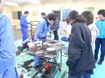 手で砂型を一つ一つ作る仕事を「手込め作業」と言います。鋳物へらで砂を切っていく技をお客様が体験!